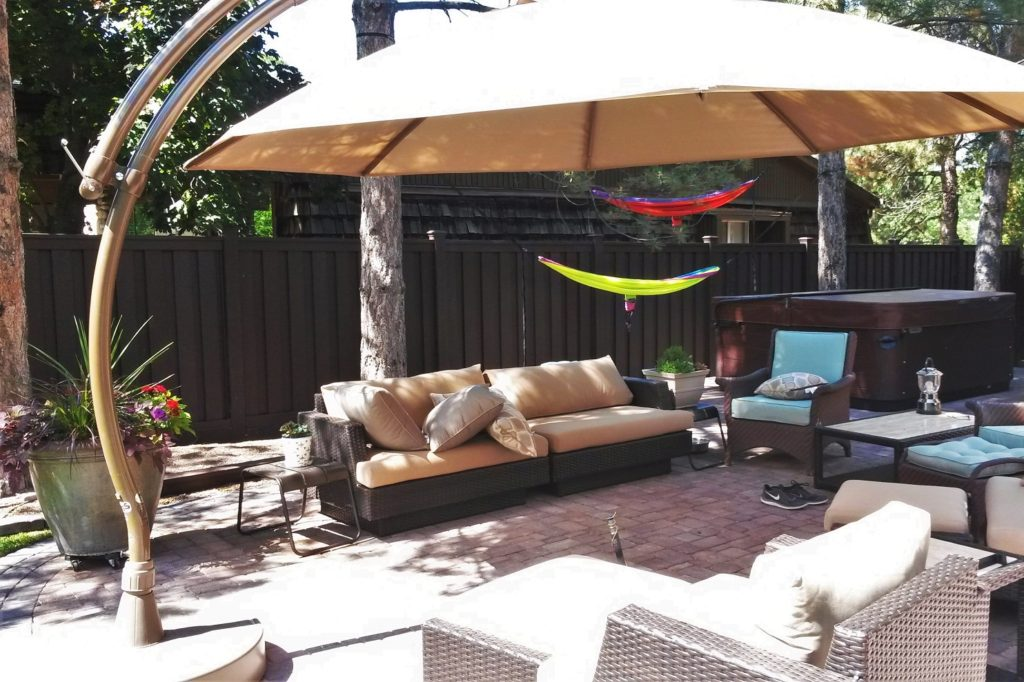 Backyard patio with furniture, shade structure, pavers, and a Trex fence